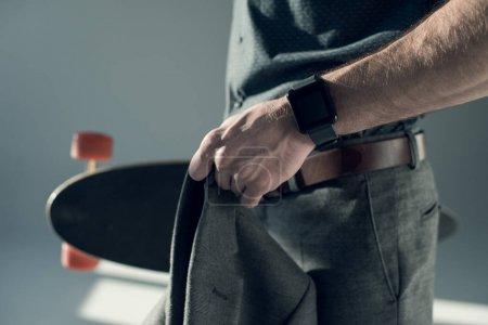 Foto de Vista lateral del hombre con estilo con smartwatch en la chaqueta de sujeción de muñeca y monopatín en gris - Imagen libre de derechos