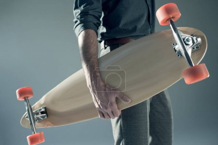 Photo pour Partial view of stylish man holding skateboard in hand on grey - image libre de droit