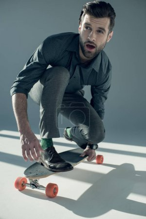 Stylish man riding skateboard