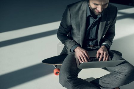 Photo for Smiling stylish businessman sitting on skateboard and typing on laptop - Royalty Free Image