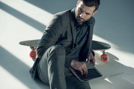 Photo for Handsome businessman sitting on floor and using laptop while looking away - Royalty Free Image