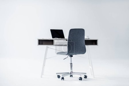 Photo for Laptop on table and empty office chair on white - Royalty Free Image