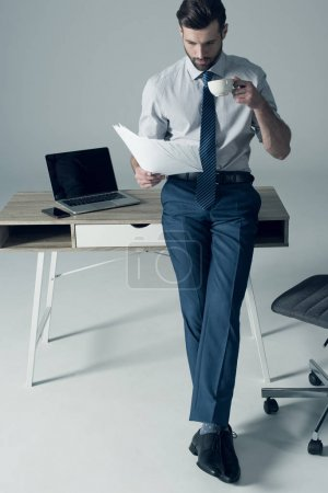 Photo for Concentrated handsome businessman standing by table and reading documents - Royalty Free Image