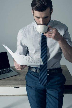 Photo pour Portrait d'un homme d'affaires élégant debout à table et buvant du café - image libre de droit