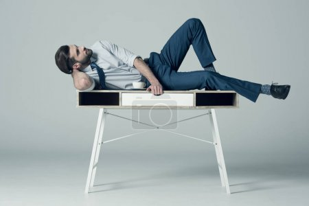 Photo pour Side view of handsome businessman lying on table with cup of coffee on grey - image libre de droit