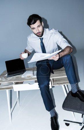 Photo pour Bel homme d'affaires tenant une tasse de café et des documents assis sur la table - image libre de droit