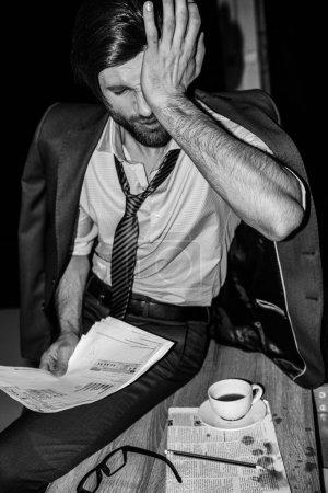 Photo pour Portrait noir et blanc d'un bel homme d'affaires fatigué travaillant avec des documents - image libre de droit