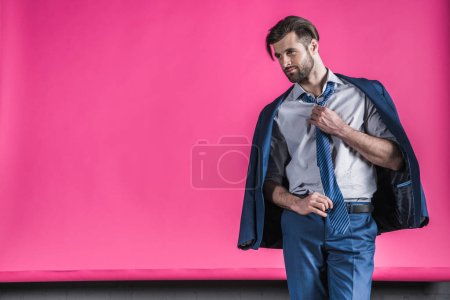 Foto de Portrait of stylish man in fashionable suit tying tie on pink - Imagen libre de derechos