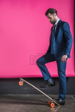 Photo for Side view of stylish hipster man in suit standing on skateboard on pink - Royalty Free Image