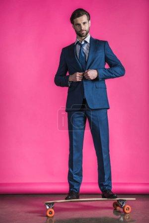 Photo pour Élégant hipster homme en costume debout sur skateboard sur rose - image libre de droit