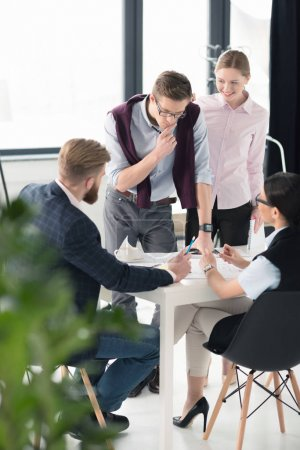 Photo for Young businessmen and businesswomen discussing business project at workplace - Royalty Free Image