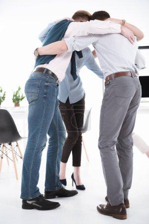 Photo pour Jeunes gens d'affaires câlins dans un bureau moderne, concept de travail d'équipe - image libre de droit