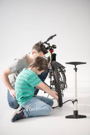 Photo for Side view of father and son inflating bicycle tire with pump on white - Royalty Free Image