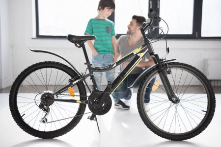 Photo for Full length view of new bicycle and happy father with son looking at each other - Royalty Free Image