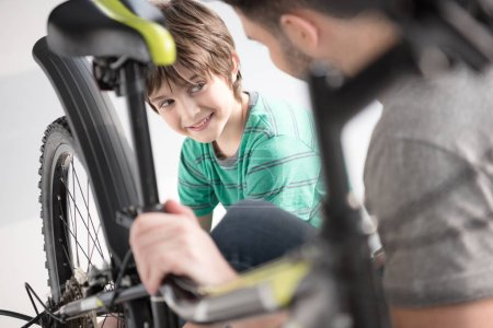 Photo for Cute smiling boy looking at father checking bicycle on white - Royalty Free Image