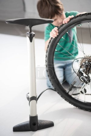 Photo for Close-up view of pump and concentrated little boy inflating bicycle tire - Royalty Free Image