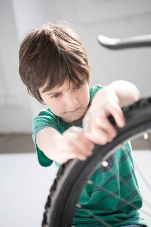 Photo for Concentrated little boy checking bicycle tyre indoors - Royalty Free Image