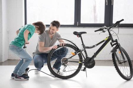 Photo for Happy father looking at son inflating bicycle tire with pump indoors - Royalty Free Image