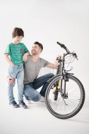 Photo for Happy father and son with new bicycle on white - Royalty Free Image