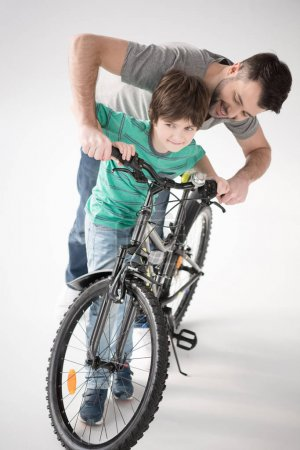 Photo for Cheerful father teaching son how to ride bicycle on white - Royalty Free Image