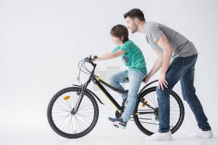 Photo pour Vue latérale du père secourable fils de monter le vélo sur blanc - image libre de droit