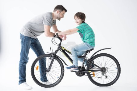 Photo for Side view of father looking at son on bicycle on white - Royalty Free Image