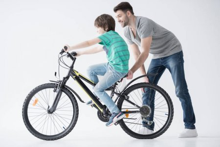 Photo for Side view of father helping son to ride bicycle on white - Royalty Free Image