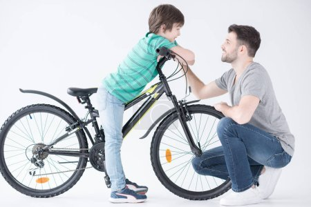 Photo for Side view of father talking with son on bicycle on white - Royalty Free Image