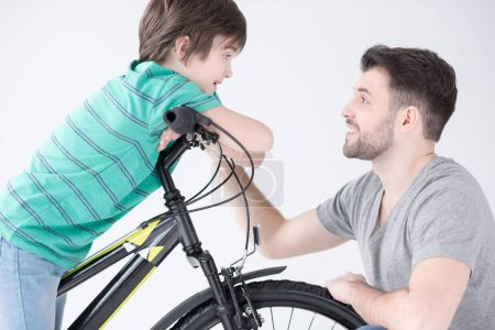 Photo for Portrait of smiling father talking with son on bicycle on white - Royalty Free Image