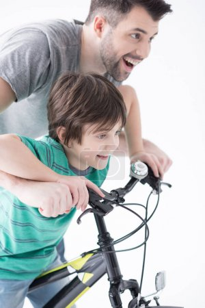 Photo for Portrait of cheerful father helping son to ride bicycle on white - Royalty Free Image