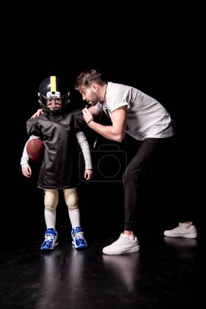 Boy playing football with trainer