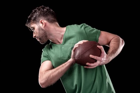 Photo for Side view of man training with rugby ball  isolated on black - Royalty Free Image