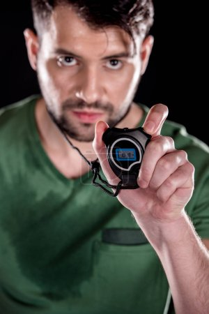 Photo for Portrait of serious man showing stopwatch and looking to camera  isolated on black - Royalty Free Image