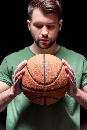 Photo for Portrait of pensive man holding basketball ball in hands isolated on black - Royalty Free Image