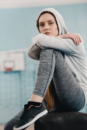 Photo for Young sporty woman sitting on pommel horse and looking at camera - Royalty Free Image
