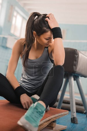 Photo for Young athletic woman in sportswear sitting on mat in sports hall - Royalty Free Image