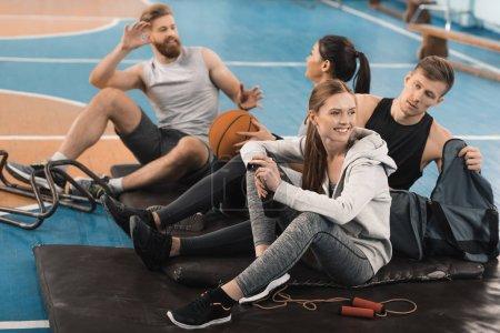 Photo pour Des jeunes sportifs souriants assis sur des nattes et parlant dans une salle de sport - image libre de droit