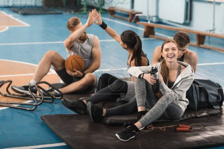 Photo for Smiling young sporty people sitting on mats and talking in sports hall - Royalty Free Image
