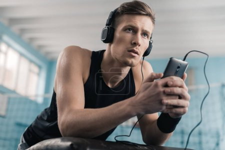 Sportsman in headphones with smartphone