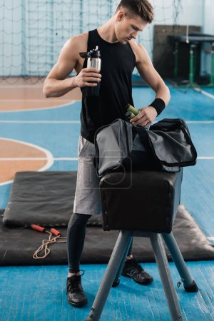 Photo for Young sportsman holding bottle and looking in bag after exercising in gym - Royalty Free Image