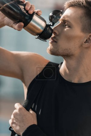 Photo for Close-up view of young sportsman drinking water from sports bottle - Royalty Free Image