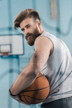 Photo for Handsome young basketball player holding ball and looking at camera - Royalty Free Image