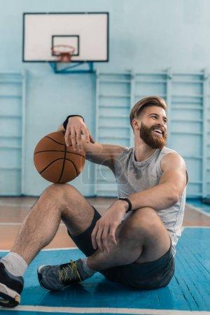 Photo pour Jeune joueur de basket barbu assis avec balle sur le sol et souriant - image libre de droit