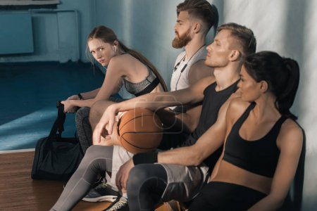 Photo for Side view of sporty men and women sitting on bench in gym - Royalty Free Image