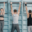 Sporty men and woman hanging on sport equipment in...
