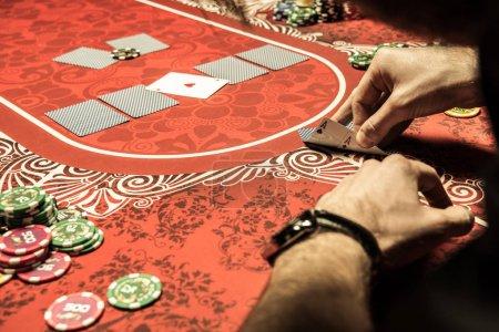 Photo pour Vue partielle de gros plan de l'homme en jouant au poker et en regardant les aces sur table - image libre de droit
