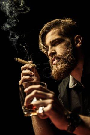 Foto de Guapo hombre barbudo sosteniendo el vaso de whisky y fumar puros en negro - Imagen libre de derechos