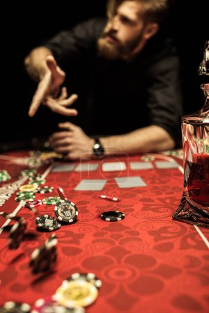 Photo for Bearded man throwing poker chips on table while playing poker - Royalty Free Image