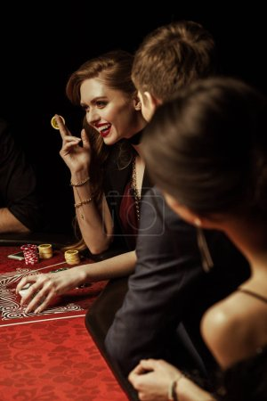 Photo for People looking at beautiful smiling woman holding casino chip at poker table - Royalty Free Image