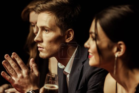 Photo for Side view of elegant young people drinking alcohol and looking away on black - Royalty Free Image